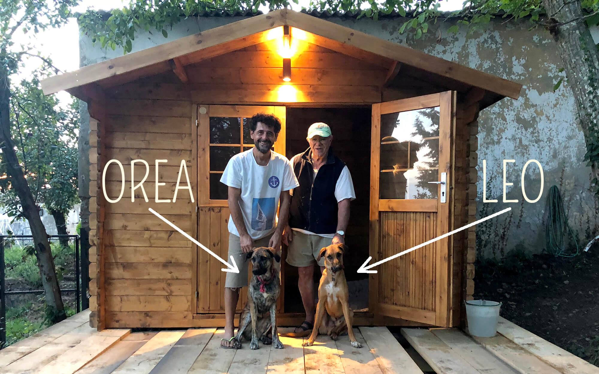 Fabrizio e Giorgio posano con i cani Leo e Orea davanti alla casetta in legno dell'area giochi per cani al Podere Camaiano